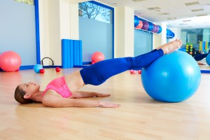 Pilates woman pelvic lift fitball exercise workout at gym indoor